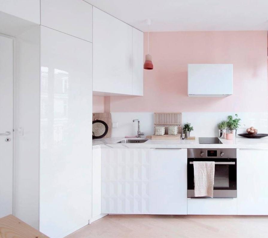 Cocina con armarios blancos y pintada en rosa
